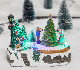 Village lumineux - Enfants qui décorent le sapin de noel